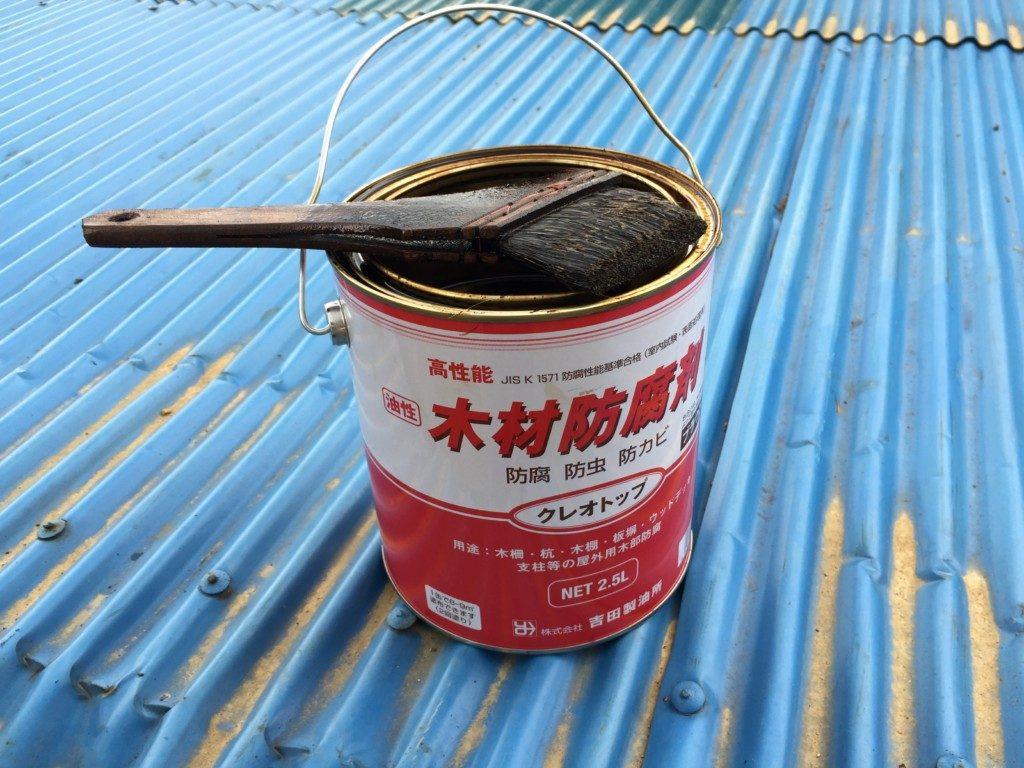 古い家の屋根の破風に木材防腐塗料を塗る